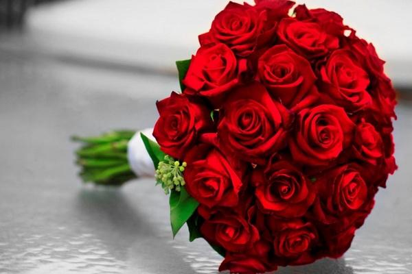 Букет из красных роз с декоративными элементами, перевязанный лентой