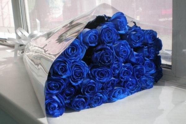Букет из синих роз в оберточной бумаге на подоконнике