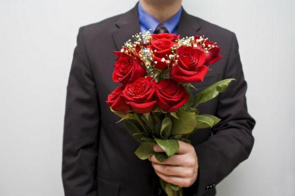 Человек в костюме с букетом роз